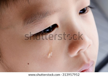 Close up on tear from young Asian boy eye that cry from his pain. - stock photo