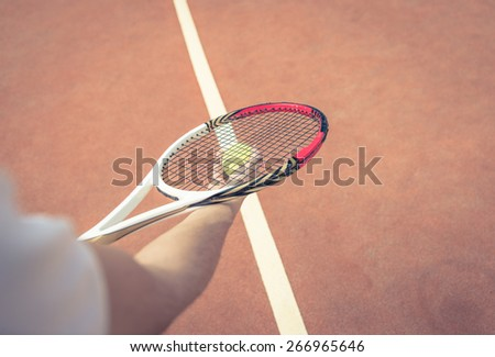 close up on tennis bat with ball. Tennis player ready for the service - stock photo