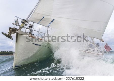Close up on the bow of a sailboat breaking through a wave - stock photo