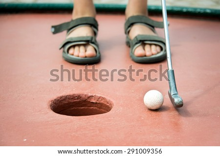 Close up on the feet of a kid playing mini golf - stock photo