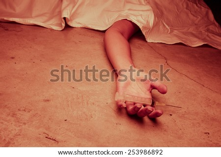 Close-up on the floor of the drugs in hand of the dead body. In the background, a young drug addict, red tone color processed - stock photo