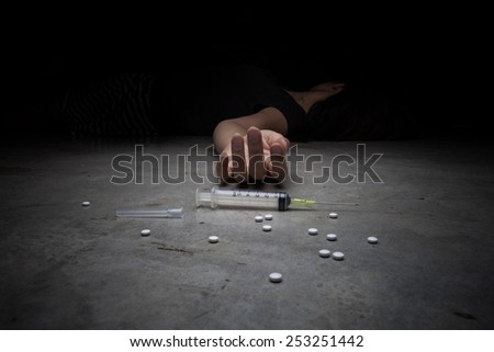 Close-up on the floor of the syringe with the drug. In the background, a young drug addict