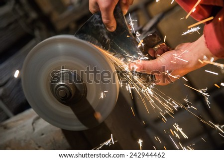 Close up on the hands of a blacksmith sharpening an axe on an electrical grinder - stock photo