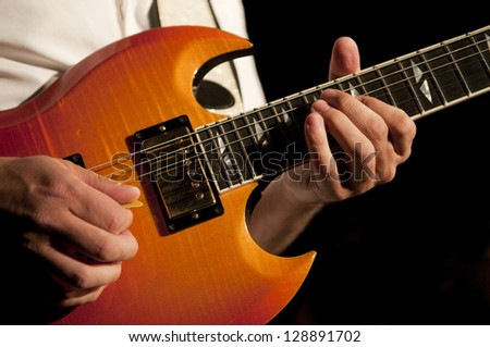 Close up on the hands of a guitar player with copy space in the background