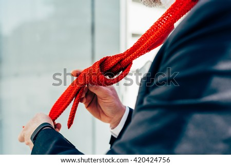 Close up on the hands of a man wearing neck tie - business, elegance concept - stock photo