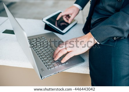 Close up on the hands of middle age caucasian businessman using technological devices like notebook leaning on his knee and tablet - business, work, multitasking concept - stock photo
