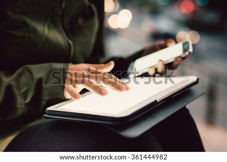 Close up on the hands of young woman using smartphone and tablet in the city night, pointing and touching the screen with her finger - technology, multitasking, communication concept - stock photo