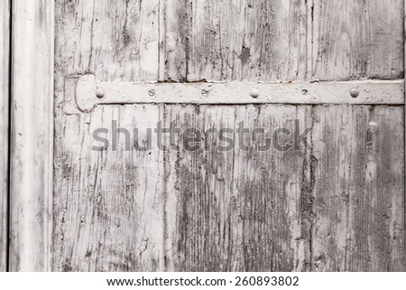 Close up on the weather-worn surface of a wooden window shutter. The texture of peeling paint is overlaying the vein of the wood. Iron mountings running horizontally across. Outdoor shot on tripod. - stock photo