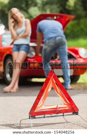 Close up on triangle warning sign with broken down car on background - stock photo