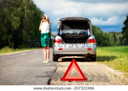 Close up on triangle warning sign with woman calling for assistance after breaking down with her car on background - stock photo