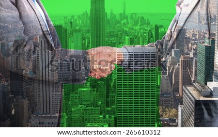 Close up on two businesspeople shaking hands against city skyline - stock photo