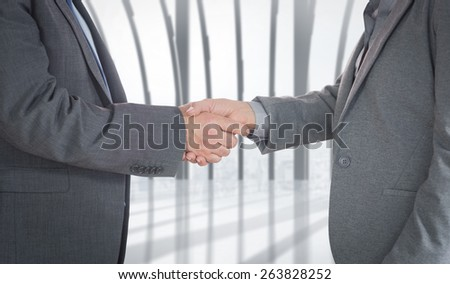 Close up on two businesspeople shaking hands against white room with large window overlooking city - stock photo