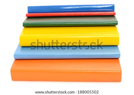 Close up on various books. Colorful books arranged in a pile isolated on white background.