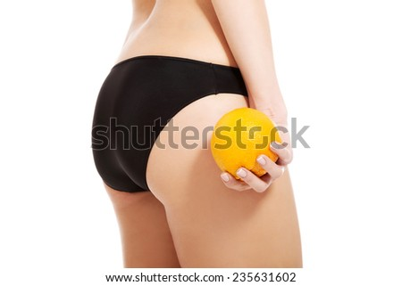 Close up on woman in panties holding yellow mango.