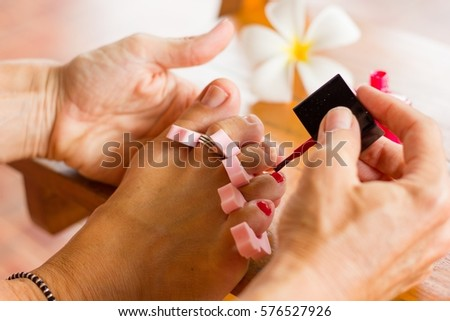 close up on womanu0027s foot getting her toenails carefully painted with pink nail polish and plumeria