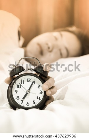 Close up on women hand reaching to turn off alarm clock. Time to wake up in morning.