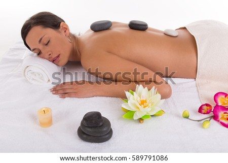 Close-up on young woman receiving hot stone massage