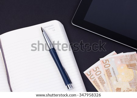 Close up open daily planner with luxury ball pen, some euro banknotes and tablet computer on black background. - stock photo