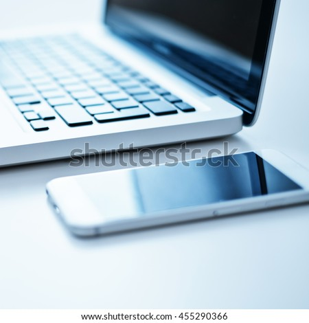 Close-up open laptop and smartphone on the table