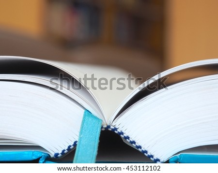 Close up open text book on wooden table in the library with blurred bookshelf background, Blue bookmark and cover