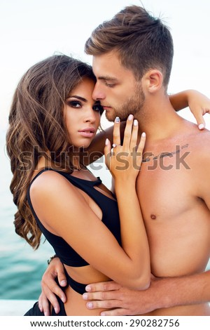 Close up  out door fashion portrait of  beautiful  sensual woman and her handsome boyfriend with perfect tan body posing on the beach. Couple in love hugging . Summer evening warm mood.