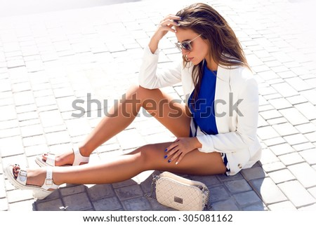 Close up outdoor fashion portrait of pretty young elegant woman walking alone at the street after business work,wearing stylish outfit and jewelry,bright sexy smoke makeup.sunglasses,heels,laying  - stock photo