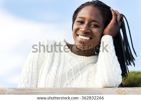 Close up outdoor portrait of attractive african teen girl with charming smile and braided hairstyle. - stock photo