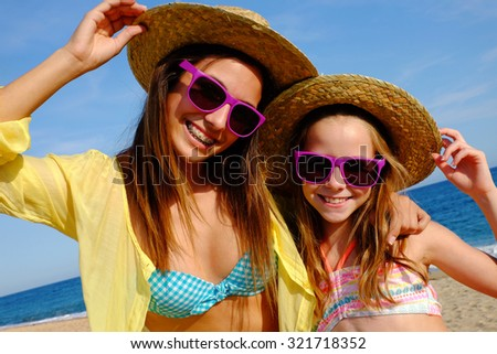 Close up outdoor portrait of attractive young mother and daughter on beach wearing straw hats and fun purple sunglasses.