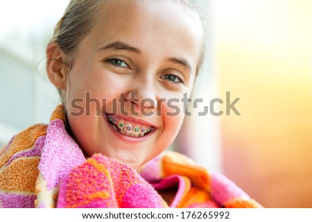 Close up outdoor portrait of cute kid with dental braces smiling.  - stock photo