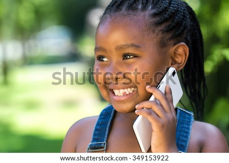 Close up outdoor portrait of cute little african girl having conversation on smart phone.