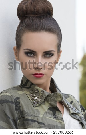 close-up outdoor portrait of pretty brunette girl with urban style and strong rock make-up. Wearing military shirt and creative hair-style  - stock photo