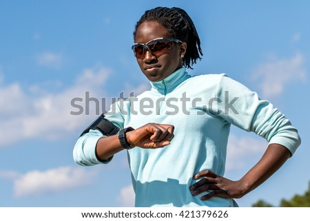Close up outdoor portrait of young african girl reviewing results on smart watch.Woman in sportswear looking at smart watch against blue sky. - stock photo