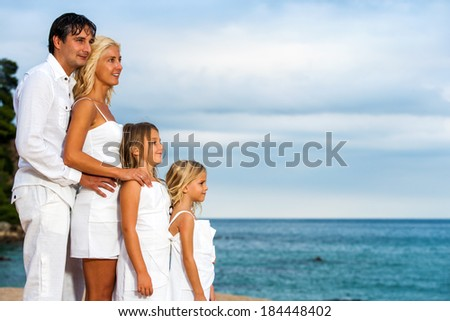 Close up outdoor portrait of young family looking aside.