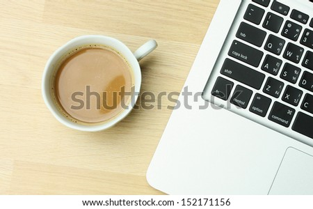 Close up over head view of a white work desk interior with a laptop computer, a cup of coffee - stock photo