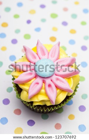 Close-up overhead view of a cupcake with pink floral pattern cream over polka dots background. - stock photo