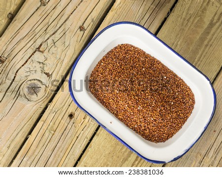 close up overhead view of red quinoa in a rustic enamelware bowl against a cracked aged wooden table top
