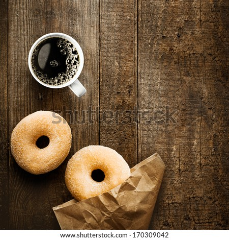 Close up overhead view of two delicious sugared ring doughnut with espresso coffee and crumpled brown paper packet on a rustic wooden surface with copyspace for a relaxing coffee break - stock photo