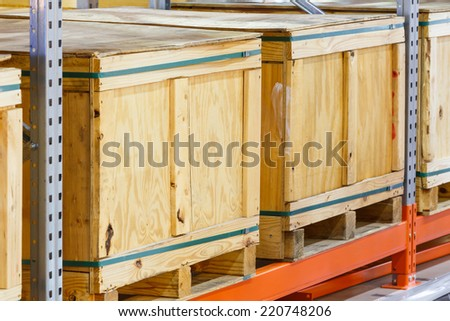 Close up paper and wooden cargo box on steel shelf system in warehouse - stock photo
