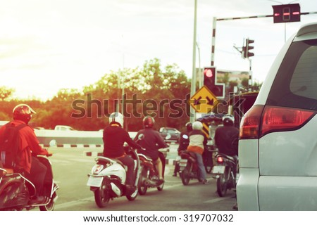 close-up part of tail light of car on urban road with people ride motorcycle stop traffic light on street - stock photo