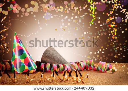 Close up Party Cone Hats and Paper Streamers on Table with Glitters Effect on Gradient Brown Background. Emphasizing Festivity Concept. - stock photo