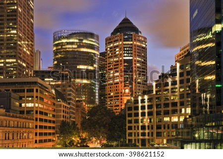 Close-up penetration into concrete jungle of the big city Sydney at sunset between tall skyscraper towers and office buildings. - stock photo