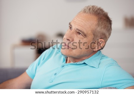 Close up Pensive Middle Aged Man in Casual Sky Blue Polo Shirt, Looking Up Seriously While Thinking So Deep. - stock photo