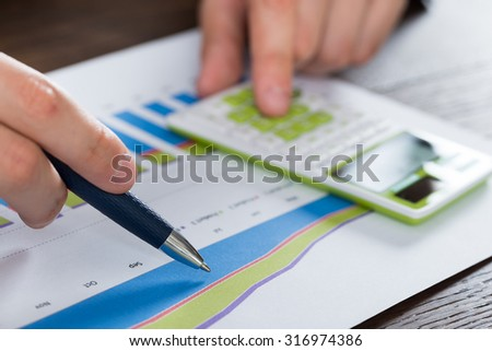 Close-up Person Hands Analyzing Financial Report With Calculator - stock photo