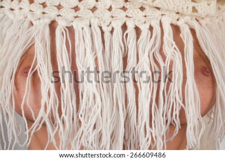 Close up photo of a beautiful and big female breasts sticking out through the fringes of knitted clothes made of white threads dumped over them so that the nipples sticking out through the fringes - stock photo