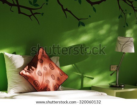 close up photo of a bed with white and red pillows in green painted wall bed room decorated with lamp and wall painting with natural light from glass windows showing garden shadows on the wall  - stock photo
