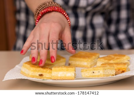 Close up photo of a female hand reaching out for a cake - stock photo