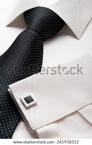 Close up photo of a folded formal white men shirt with a black tie - stock photo