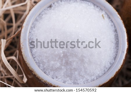 Close up photo of a food ingredients in a clay cup - white sugar placed on a wooden shavings.