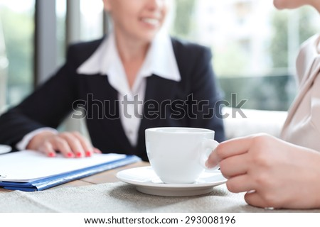 Close up photo of a hand of a woman holding a cup of coffee and her business partner, in a restaurant during business lunch, selective focus - stock photo