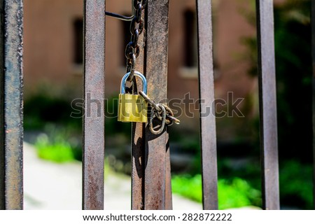 Close up photo of a padlock with big thick chain lock on a black metal gate.  Padlock was photographed outside in Szeged, Hungary.The gate was locked. Selective focus.  - stock photo
